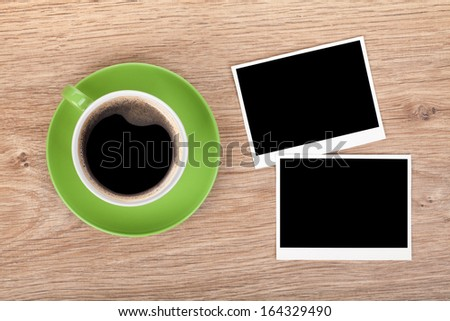Cup of coffee and two photo frames on wooden table - stock photo