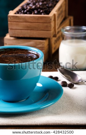 Cup of coffee and wooden containers filled with cofee beans on the rust background. Cane sugar. Low light. - stock photo