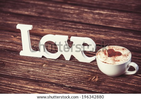 Cup of coffee and word Love on wooden table. - stock photo