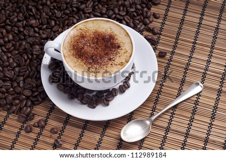 Cup of coffee arranged with  fresh roasted coffee beans on a wooden background - stock photo