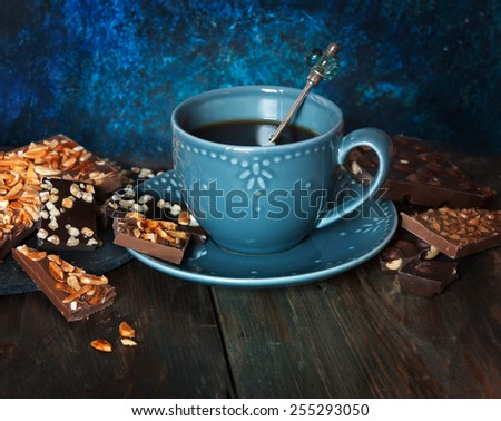 Cup of coffee, assortment of  chocolates on wooden table - stock photo