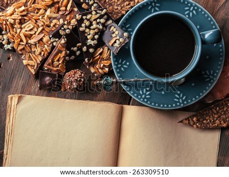 Cup of coffee, assortment of fine chocolates dark, milk chocolate and book for notes on wooden table - stock photo