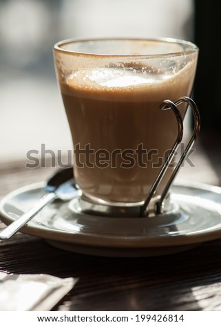 Cup of coffee backlit on the table, close-up. Shallow dof focus on the cup in front. - stock photo