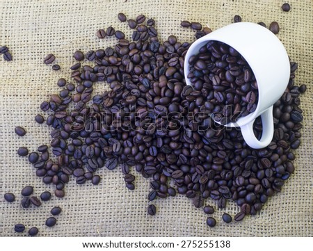 Cup of coffee beans on burlap hessian sacking texture background - stock photo