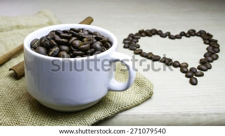 cup of coffee beans with heart coffee beans on the table - stock photo