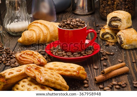 Cup of Coffee Beans with Pastry on brown wood table background