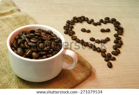 cup of coffee beans with smiling coffee beans on the table - stock photo