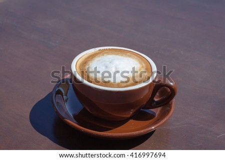 Cup of coffee cappuccino art on wood table/ vintage style