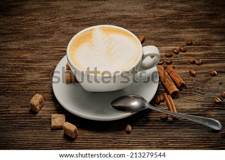 Cup of coffee cappuccino with brown sugar on a wooden table. - stock photo