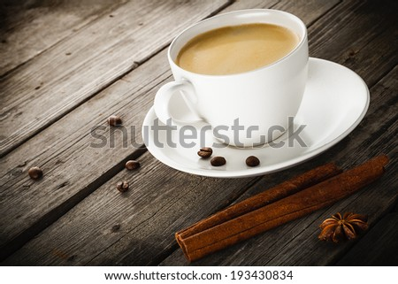 cup of coffee cinnamon sticks and anise star on old wooden table. - stock photo