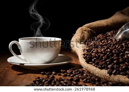 cup of coffee, coffee beans, bag on a wood table on a black background - stock photo