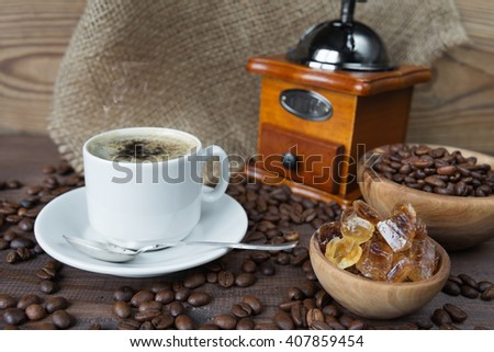 Cup of coffee, coffee mill and wooden bowl with sugar on the wooden background with coffee beans - stock photo
