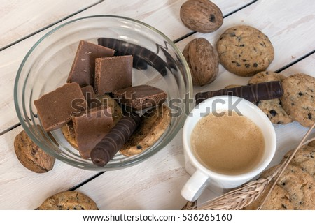 Cup of coffee, cookies, walnut and chocolate on the white wooden background