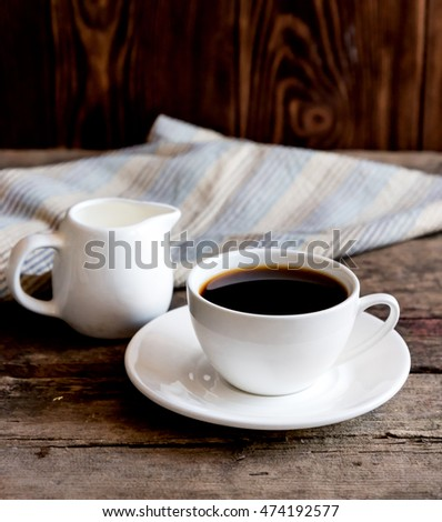 Cup of coffee,cream and napkin on wooden background