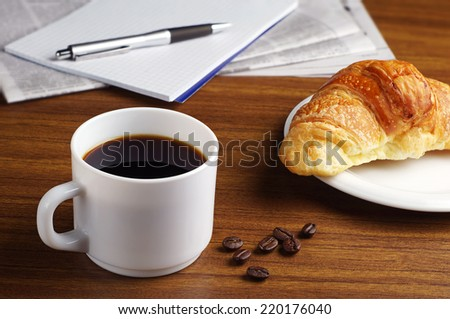 Cup of coffee, croissant, newspaper and notepad on wooden table - stock photo