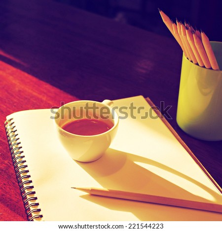 Cup of coffee espresso on the notebook and pencil vintage color tone