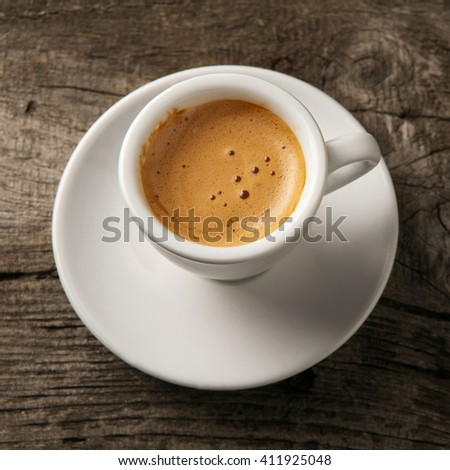 Cup of coffee espresso with foam on the old wooden background, top view - stock photo