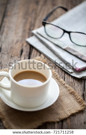 cup of coffee, glasses and newspaper on wooden table
