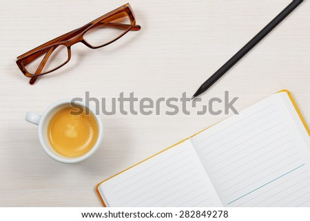 cup of coffee, glasses and notebook on office desk - stock photo