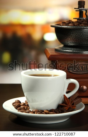 cup of coffee, grinder and coffee beans in cafe