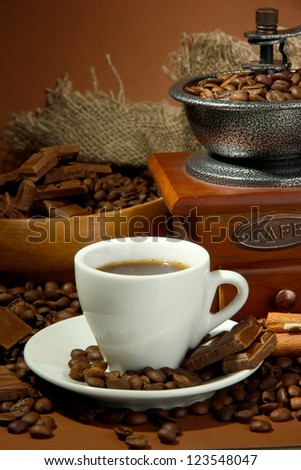 cup of coffee, grinder, turk and coffee beans on brown background