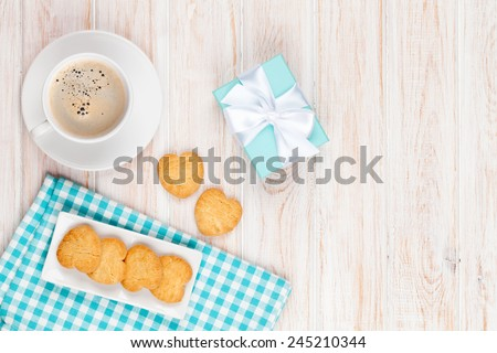 Cup of coffee, heart shaped cookies and gift box on white wooden table with copy space - stock photo