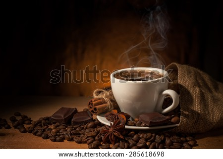 Cup of coffee in coffee beans on brown background