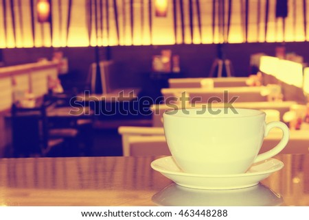 Cup of coffee in coffee shop,vintage effect blur style