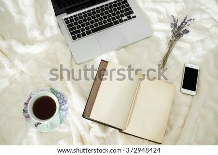 Cup of coffee, laptop, smartphone, vintage notebook and dry lavender in bed, morning light