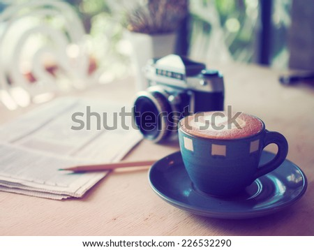cup of coffee latte and classic camera  in coffee shop vintage color - stock photo