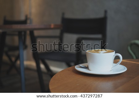 cup of coffee latte art on the wooden desk in coffee shop cafe with vintage color tone filter background