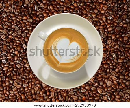 Cup of coffee latte on coffee beans background - stock photo