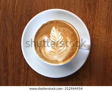 Cup of coffee latte with leaf design art in froth, on a wooden table and viewed from top.
