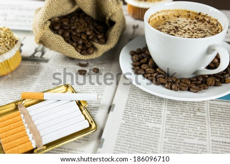 Cup of coffee, muffins and roasted beans arranged on a newspaper - stock photo