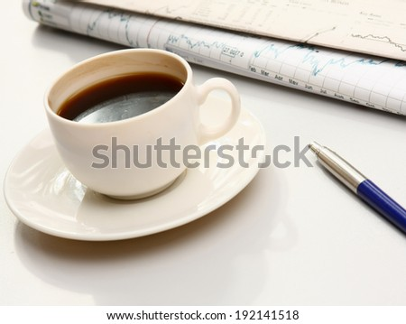 cup of coffee near the laptop and newspapers - stock photo