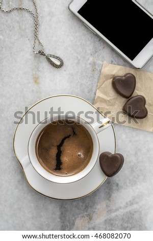 Cup of coffee , necklaces and chocolate  on table, from above
