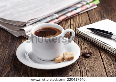 Cup of coffee, newspaper and notepad on old wooden table - stock photo
