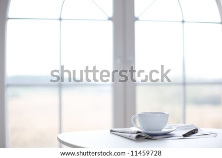 Cup of coffee, newspaper and pen on the table in front of window / copyspace - stock photo