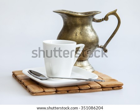 Cup of coffee of espresso and ancient metal small jug for milk