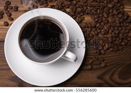 Cup of coffee on a background coffee beans on wooden table