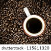 Cup of coffee on a bed of coffee beans - stock photo