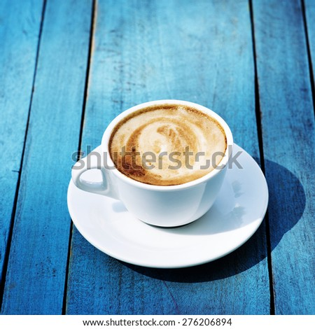 Cup of coffee on a bright wooden table background - stock photo