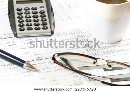 Cup of coffee on a financial report .(Coffee break) - stock photo