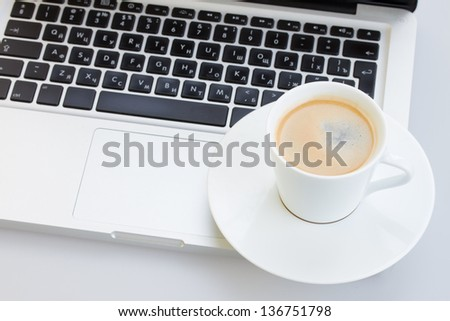 Cup of coffee  on a gray laptop keyboard - stock photo