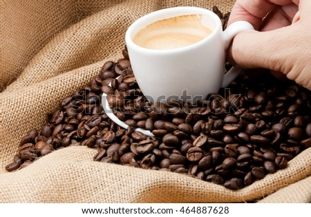 cup of coffee on a sack full of toasted coffee beans