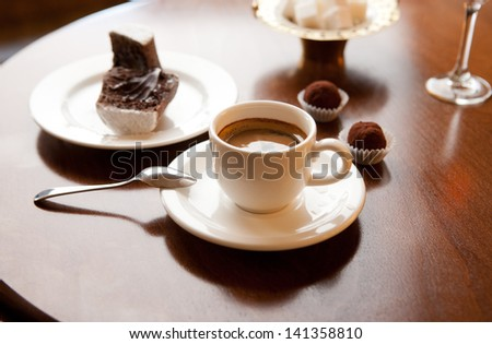 Cup of coffee on a table. Spoon, candy, cake - stock photo