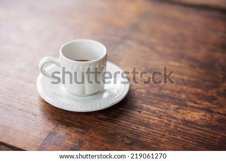 Cup of coffee on a textured wooden table - stock photo