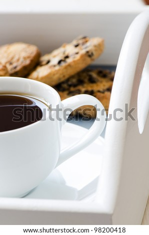 Cup of coffee on a tray with chocolate chip cookies on background - stock photo