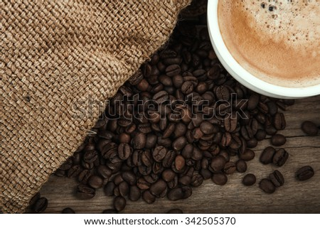 cup of coffee on a wooden board with burlap