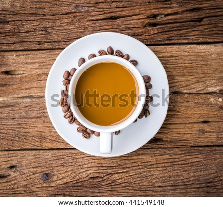 Cup of coffee on a wooden desk with coffee beans - stock photo